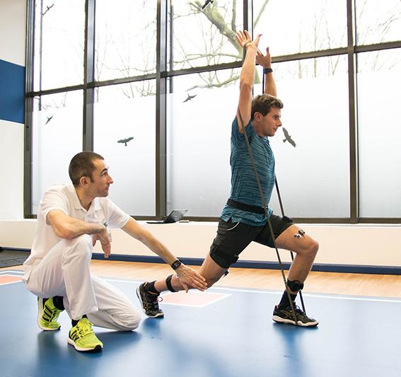 Sportler mit EMG Sensoren beim Ausfallschritt und Therapeut