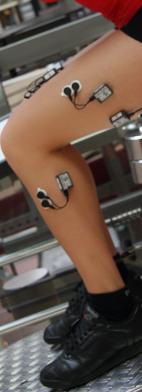 Beine einer Frau mit EMG Sensoren sitzend auf einer Trainingsmaschine