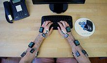 Arme mit EMG- und Inertialsensoren am Schreibtisch und Tastatur